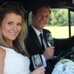A happy couple in car after wedding reception